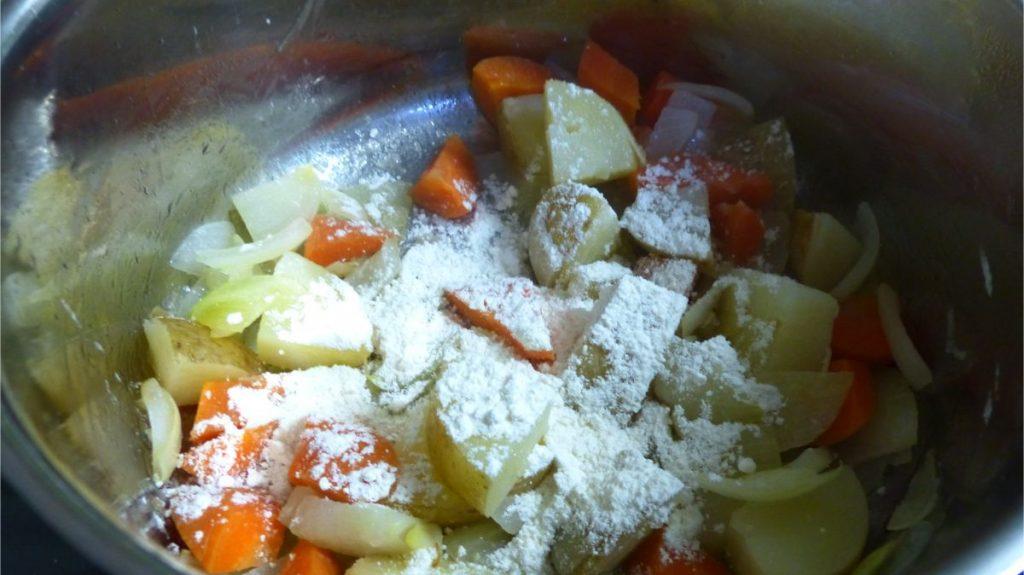 鍋にじゃがいも、にんじん、薄力粉を入れる