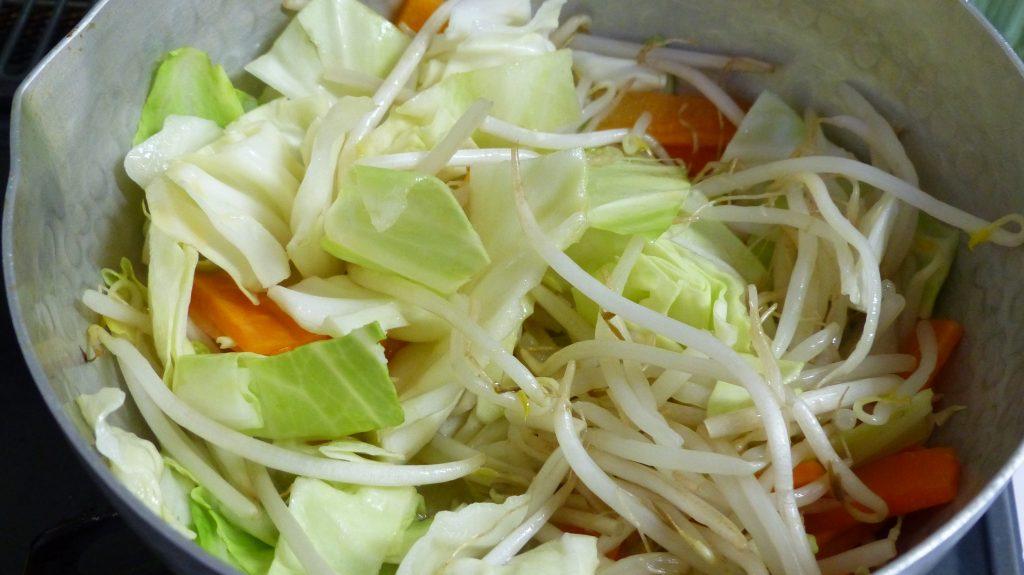 鍋にゴマ油を引き、野菜を炒める
